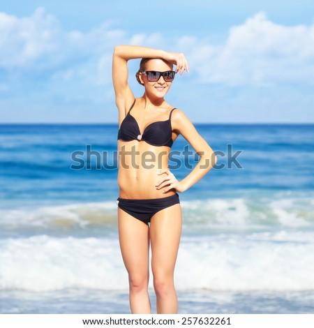 portrait of young beautiful woman in black bikini and sunglasses posing on blue - stock photo