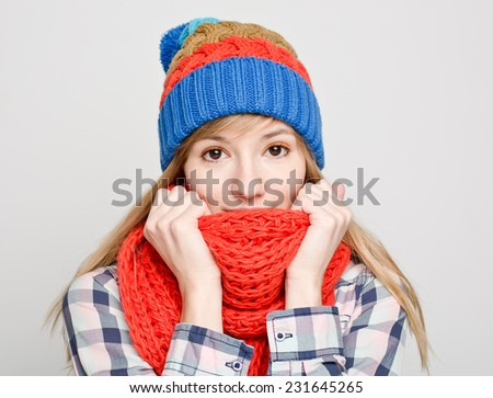 Portrait of young beautiful woman in cozy red scarf and winter hat - stock photo