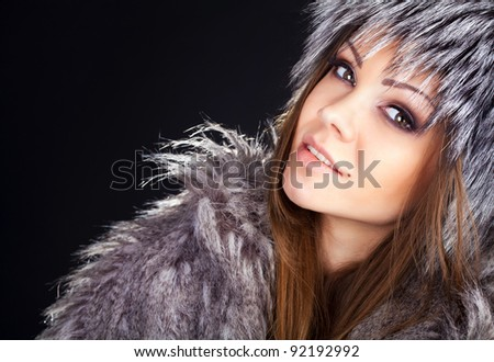 Portrait of young beautiful woman in furs isolated