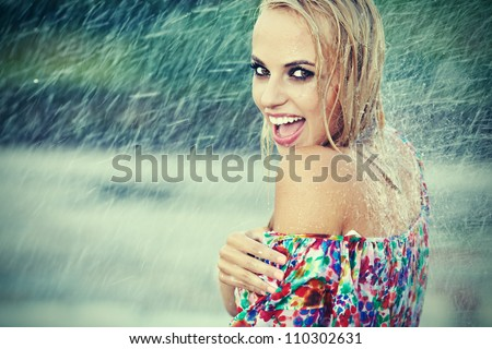 portrait of young beautiful woman in rain - stock photo