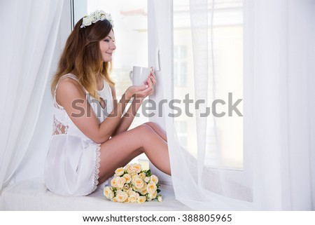 portrait of young beautiful woman in short white dress with flowers and cup of tea sitting on window sill