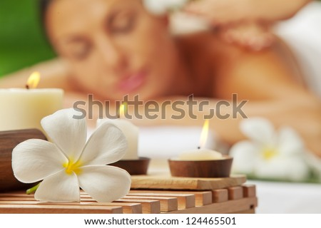 portrait of young beautiful woman in spa environment. blurred face, focused on flower. - stock photo