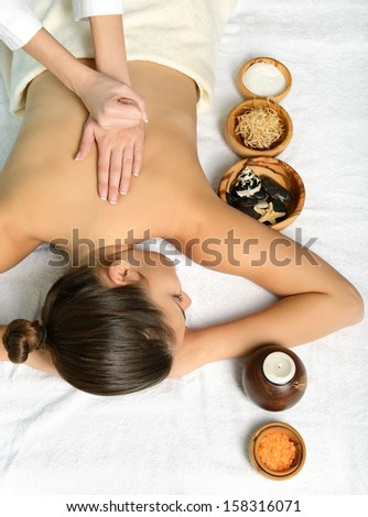 portrait of young beautiful woman in spa environment gets massage - stock photo