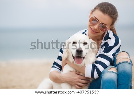 portrait of young beautiful woman in sunglasses sitting on sand beach hugging golden retriever dog. girl with dog by sea. happiness and friendship. pet and woman.woman playing with dog on sea shore - stock photo