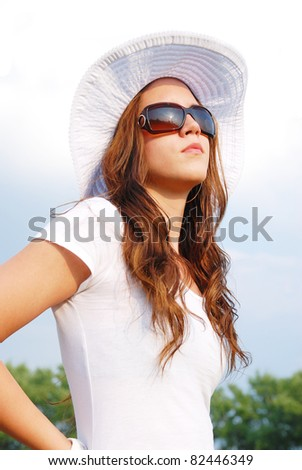 Portrait of young beautiful woman in white hat and sunglasses - stock photo