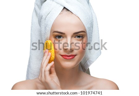 Portrait of young beautiful woman in white towel with bath sponge cleaning her face. Isolated on white background - stock photo