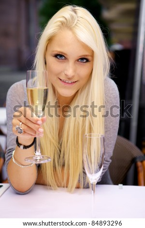 Portrait of young beautiful woman lifting a glass of champagne - cheers! - stock photo