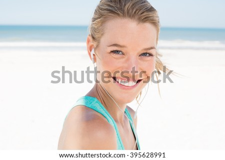 Portrait of young beautiful woman listening to music at beach. Close up face of smiling blonde woman with earphone looking at camera. Girl running at beach and listening to music. - stock photo