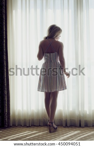 portrait of young beautiful woman looking in the window - stock photo
