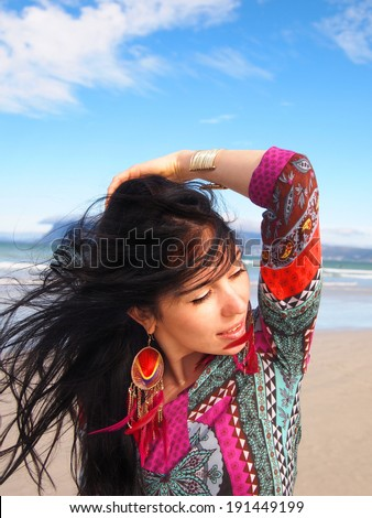 Portrait of young beautiful woman looking into the distance on the Sunrise beach in Cape Town. South Africa. Blowing long hair. Fashion shooting. Oriental style. Boho-chic.       - stock photo
