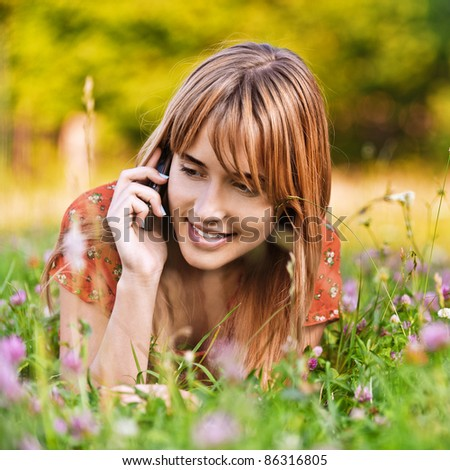 Portrait of young beautiful woman lying on grass and speaking on telephone at summer green park. - stock photo