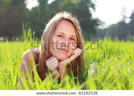 Portrait of young beautiful woman lying on green grass. Relaxation