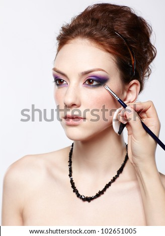 portrait of young beautiful woman maked up by makeup artist artist's hand on violet eyeshadow - stock photo