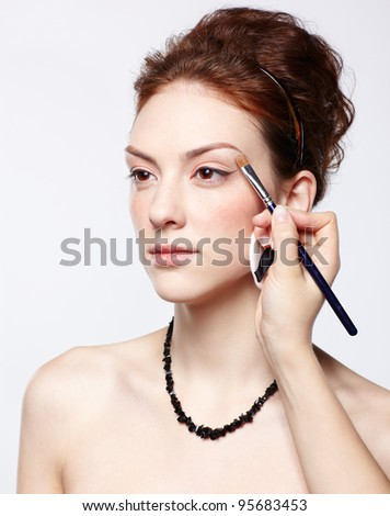 portrait of young beautiful woman maked up by makeup artist's hand putting on eyeshadow - stock photo