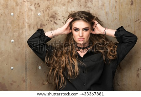Portrait of young beautiful woman near the wall. Model runs his hands through his hair. Long wavy hair. Modern appearance, professional makeup - stock photo