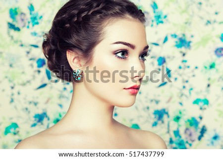 Portrait of young beautiful woman on a background of flowers. Fashion photo. Jewelry and hairstyle. Perfect makeup
