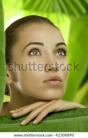 portrait of young beautiful woman on green leafs back