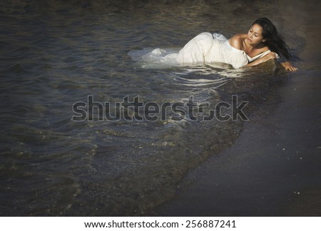 Portrait of young beautiful woman outdoors near sea