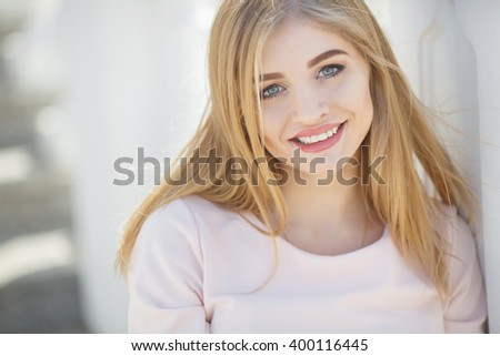 Portrait Of Young  Beautiful Woman outdoors. Portrait Of Young Smiling Beautiful Woman. Close-up portrait of a fresh and beautiful young fashion model posing in the city street