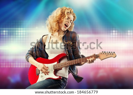 Portrait of young beautiful woman playing the guitar. Happiness concept. - stock photo
