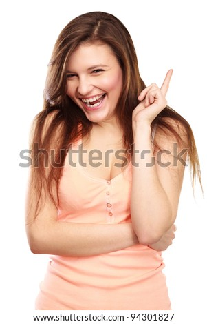 Portrait of young beautiful woman pointing up at copyspace over white background