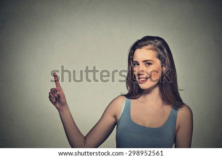 Portrait of young beautiful woman pointing with finger up to side at empty copy space. Standing happy smiling girl isolated on gray wall background. Advertisement of product concept   - stock photo