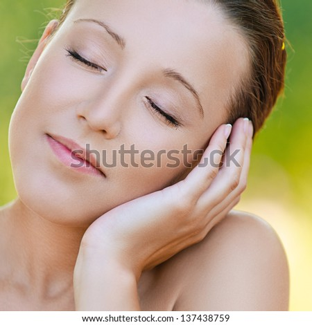 Portrait of young beautiful woman propping up her face at summer green park. - stock photo