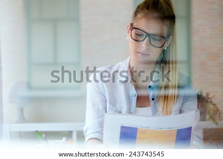 Portrait of young beautiful woman reading newspaper at home. - stock photo