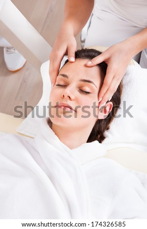 Portrait Of Young Beautiful Woman Receiving Head Massage At Spa - stock photo