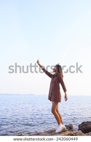 portrait of young beautiful woman rising up smart phone to sky use for feeling of human communication by hi-technology on wireless mobile phone  - stock photo