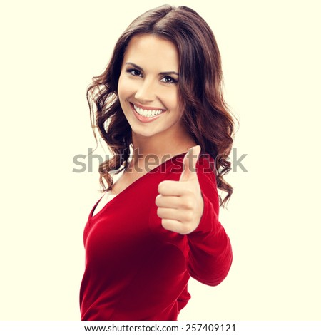 Portrait of young beautiful woman showing thumbs up gesture - stock photo