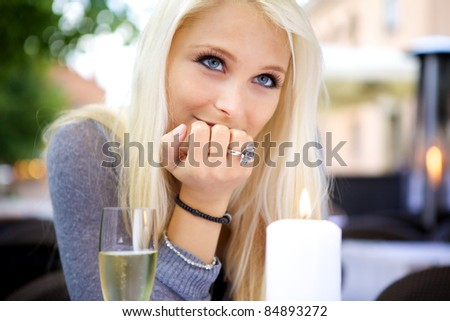 Portrait of young beautiful woman sitting at a dining table with a glass of champagne. - stock photo
