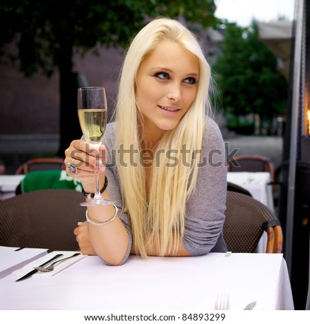 Portrait of young beautiful woman sitting on a restaurant drinking champagne. - stock photo