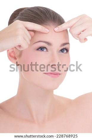 portrait of young beautiful woman squeezing acne or pimple isolated on white background - stock photo