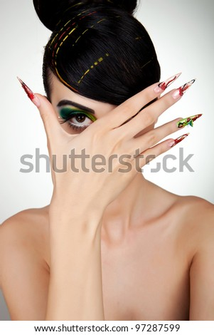 portrait of young beautiful woman touching face with manicured fingers - stock photo