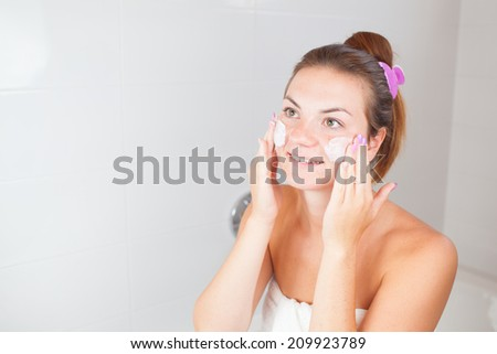 Portrait of young beautiful woman using cosmetics cream on her face - stock photo
