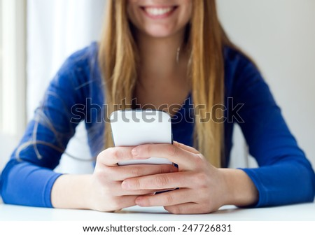 Portrait of young beautiful woman using her mobile phone at home. - stock photo