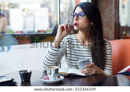 Portrait of young beautiful woman using her mobile phone in coffee. - stock photo