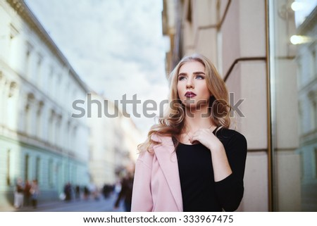 Portrait of young beautiful woman walking in the city. Street fashion concept.  - stock photo
