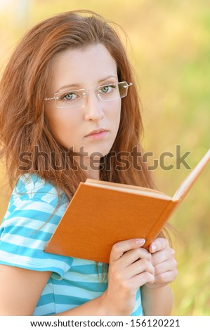 Portrait of young beautiful woman wearing glasses and carefully read book, on green background summer nature. - stock photo