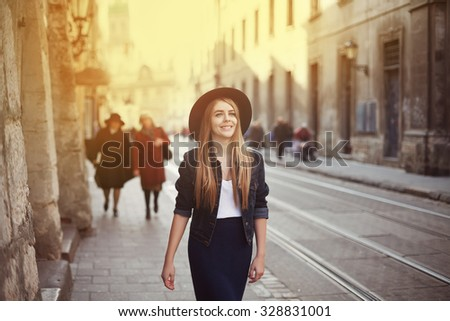Portrait of young beautiful woman wearing hat walking in the old city. Street fashion concept. Toned  - stock photo