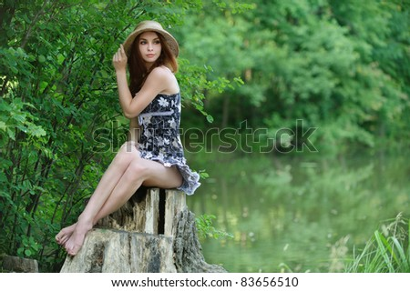 Portrait of young beautiful woman wearing straw hat and black dress, sitting on stump against lake at summer green park. - stock photo