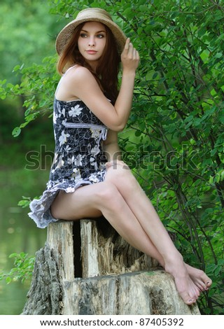 Portrait of young beautiful woman wearing straw hat and black dress, sitting on stump against lake at summer green park.