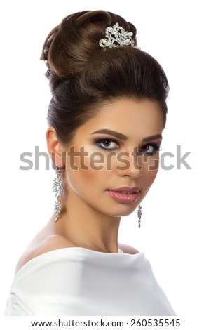 Portrait of young beautiful woman wearing white dress isolated over white background. Wedding coiffure and make-up. - stock photo