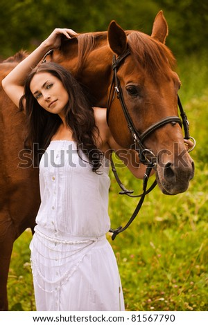 Portrait of young beautiful woman wearing white dress standing at summer green park with brown kind horse. - stock photo