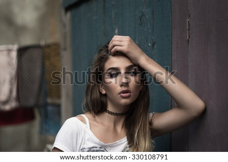 Portrait of young beautiful woman with artistic makeup. Urban vintage background. - stock photo