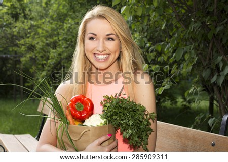 Portrait of young beautiful woman with bare shoulders holding a vegetable on green background summer nature. - stock photo