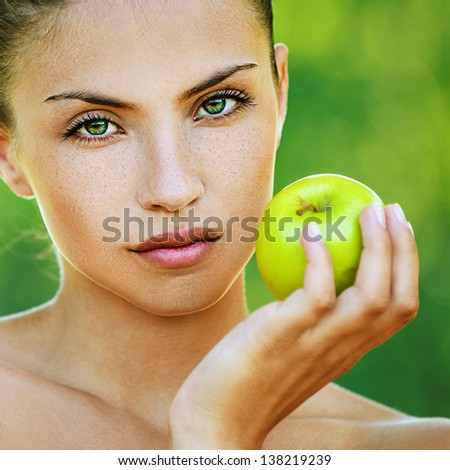 Portrait of young beautiful woman with bare shoulders holding an apple, on green background summer nature. - stock photo