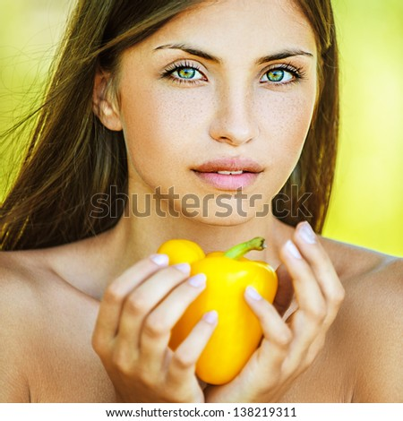 Portrait of young beautiful woman with bare shoulders holding yellow pepper, on green background summer nature. - stock photo