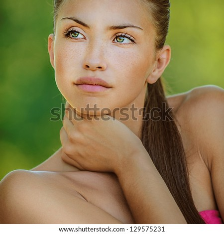 Portrait of young beautiful woman with bare shoulders looked thoughtfully at thoron, on green background summer nature.